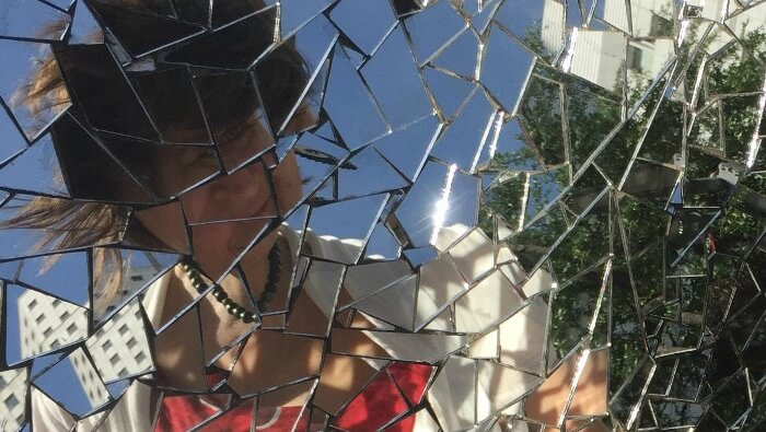 woman looks at her image in a shattered mirror