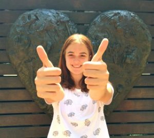 Girl in front of heart giving two thumbs up
