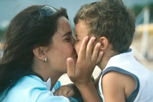Loving Mom kissing her happy young son with special needs